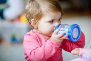 Baby girl drinking from milk bottle